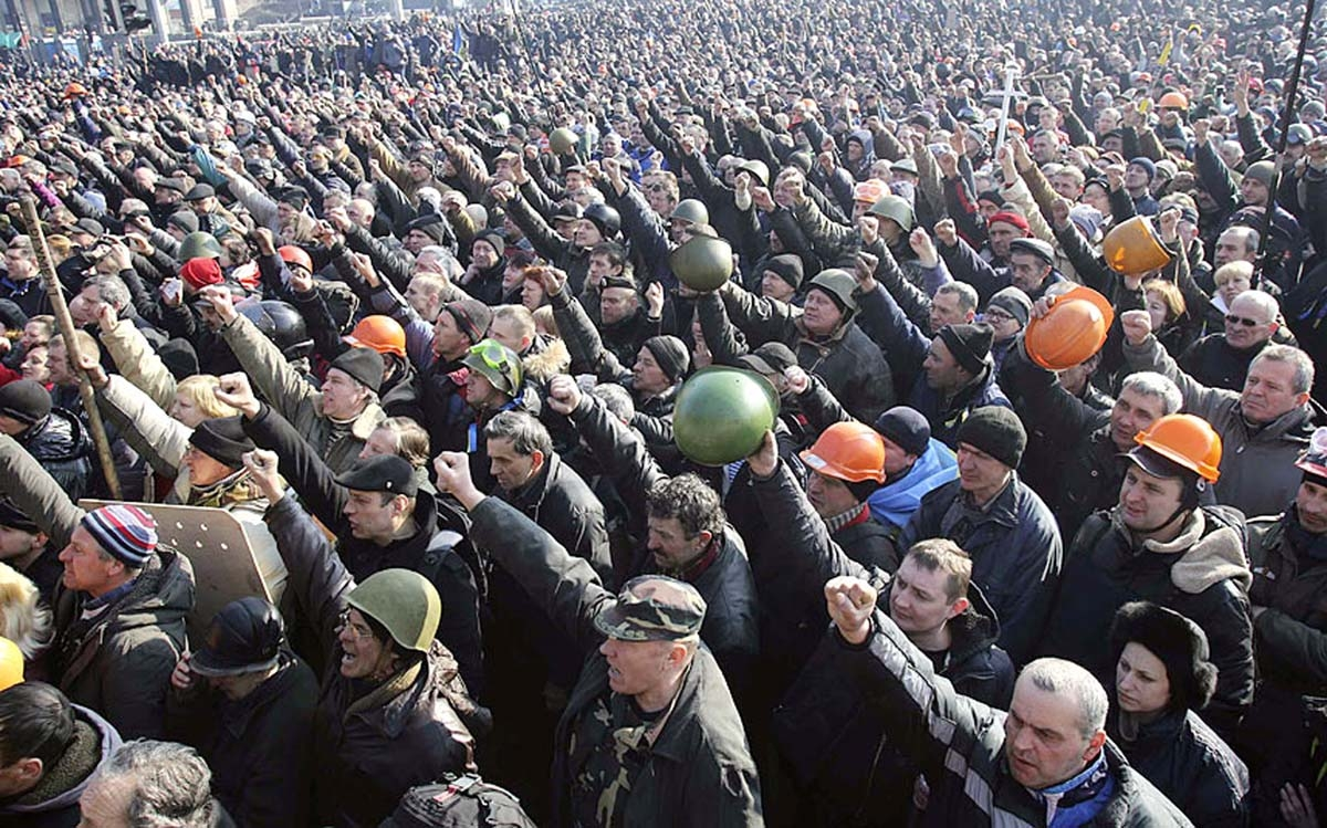 People cheer as they listen to police officers from Lviv who have joined anti-government protesters during a rally in Independence Square in Ukraine.