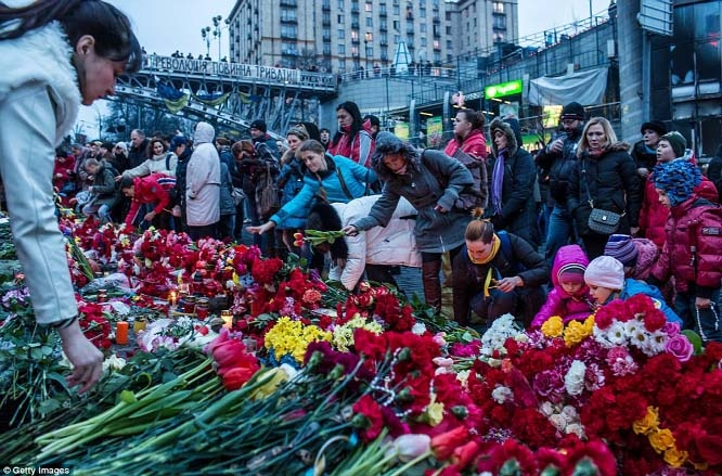 People place flowers at a makeshift memorial as they gather to commemorate the victims of the recent clashes in central Kiev.