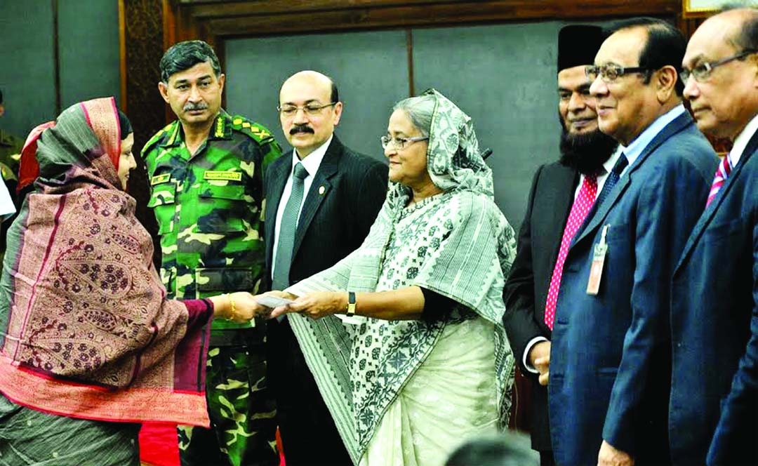 Prime Minister Sheikh Hasina, in presence of A. Rouf Chowdhury, Chairman of Bank Asia and A.M. Nurul Islam, Vice Chairman at the Prime Minister's Office, is handing over a cheque of Tk.4.80 lakh to Mrs. Rashida Kabir Reba, widow of Major (late) Md. Humayun Kabir Sarker who was brutally killed in BDR carnage at Pilkhana in 2009.