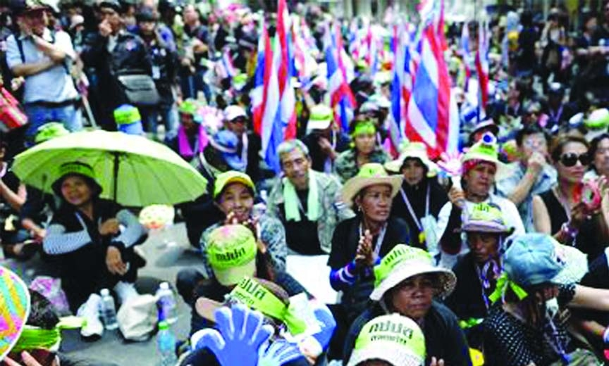 Thai anti-government protesters wave clappers as they rally outside the national police headquarters in downtown Bangkok on Wednesday.