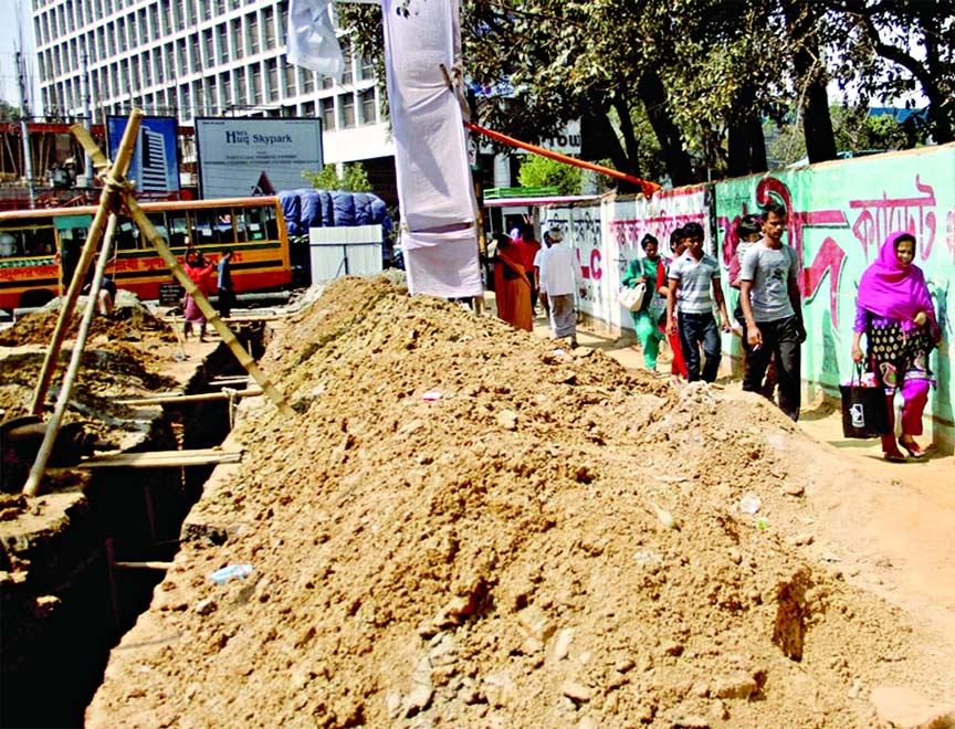 People have to face serious inconveniences while passing through the road which was dug by WASA for development works in city's busy Shyamoli area. This photo was taken on Wednesday.