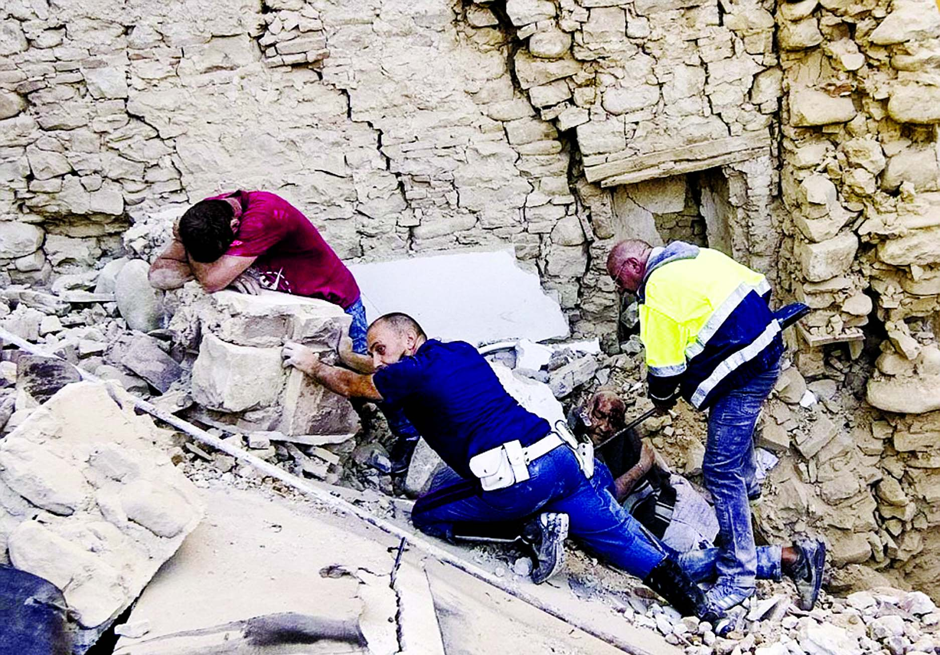 A man cries (left) as the injured local is delicately pulled from the rubble while another rescuer prevents bricks from sliding down on top of him.