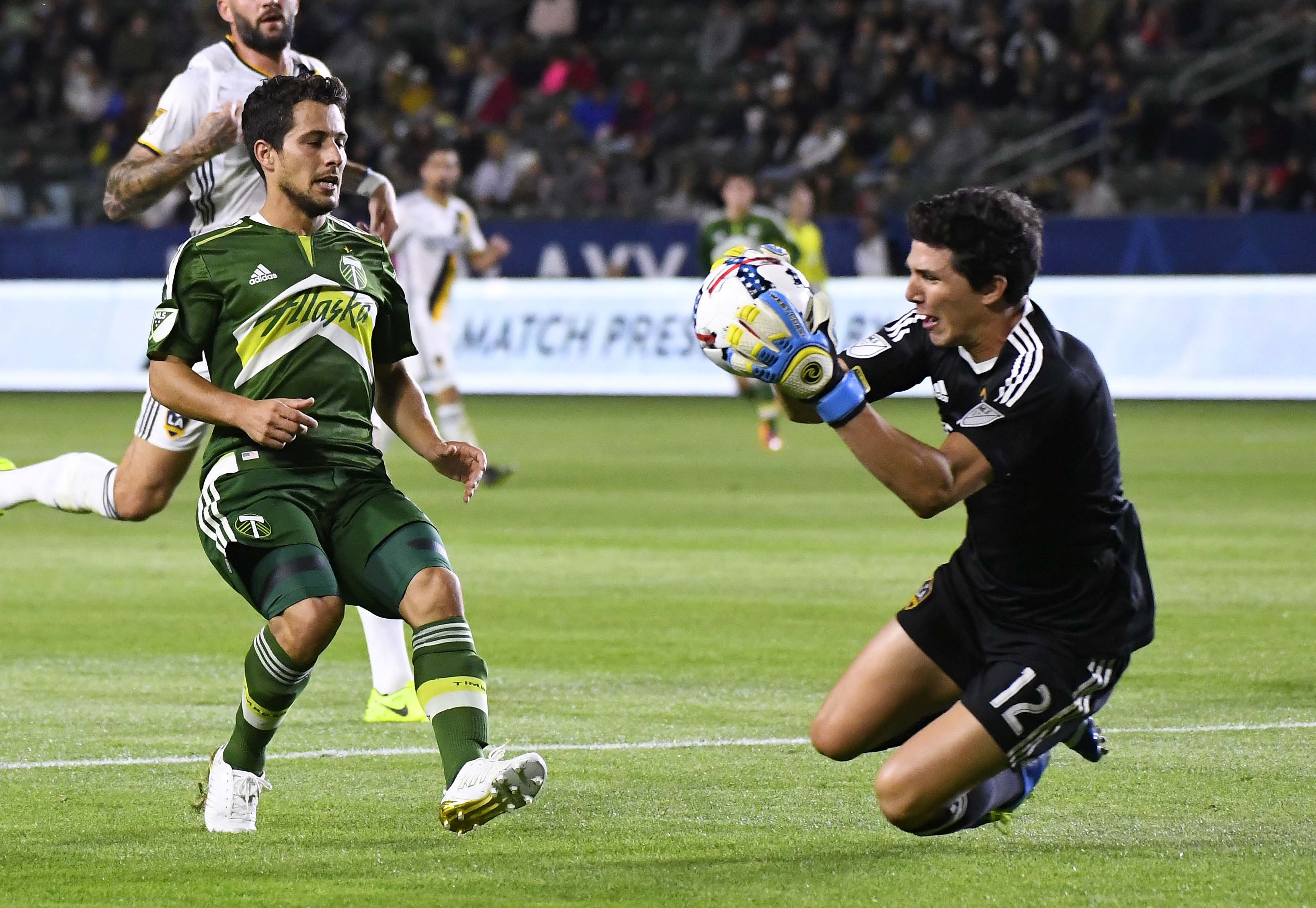 Los Angeles Galaxy goalkeeper Brian Rowe, right, stops a shot by Portland Timbers midfielder Sebastian Blanco during the first half of a preseason MLS soccer match in Los Angeles on Saturday.