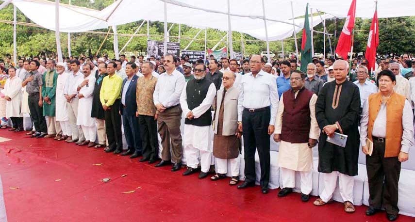 Liberation War Affairs Minister AKM Mozammel Haque, among others, stands in a solemn silence marking the Genocide Day at Shikha Chirantan (Eternal Flame) in the city