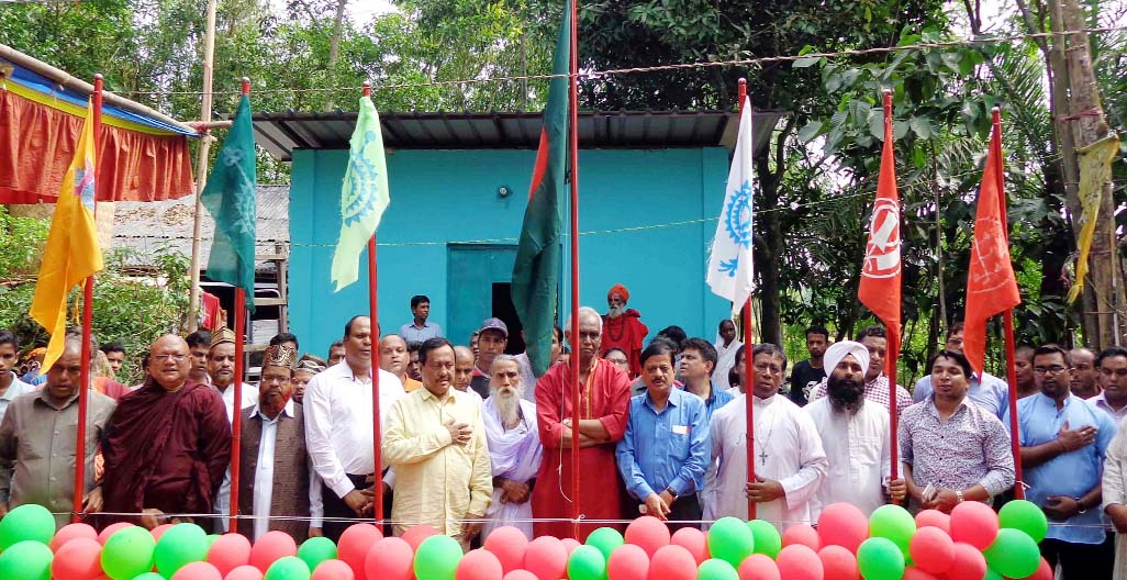 Principal of Shrine Swami Nittananda Puri Moharaj and General Secretary of  Inter Religion Harmony  freedom fighter Monoranjan Ghosal alongwith other  guests hoisting flags of all religions in the inter- religion conference  at Kelishahor,  Patiya in Chittagong on Thursday.