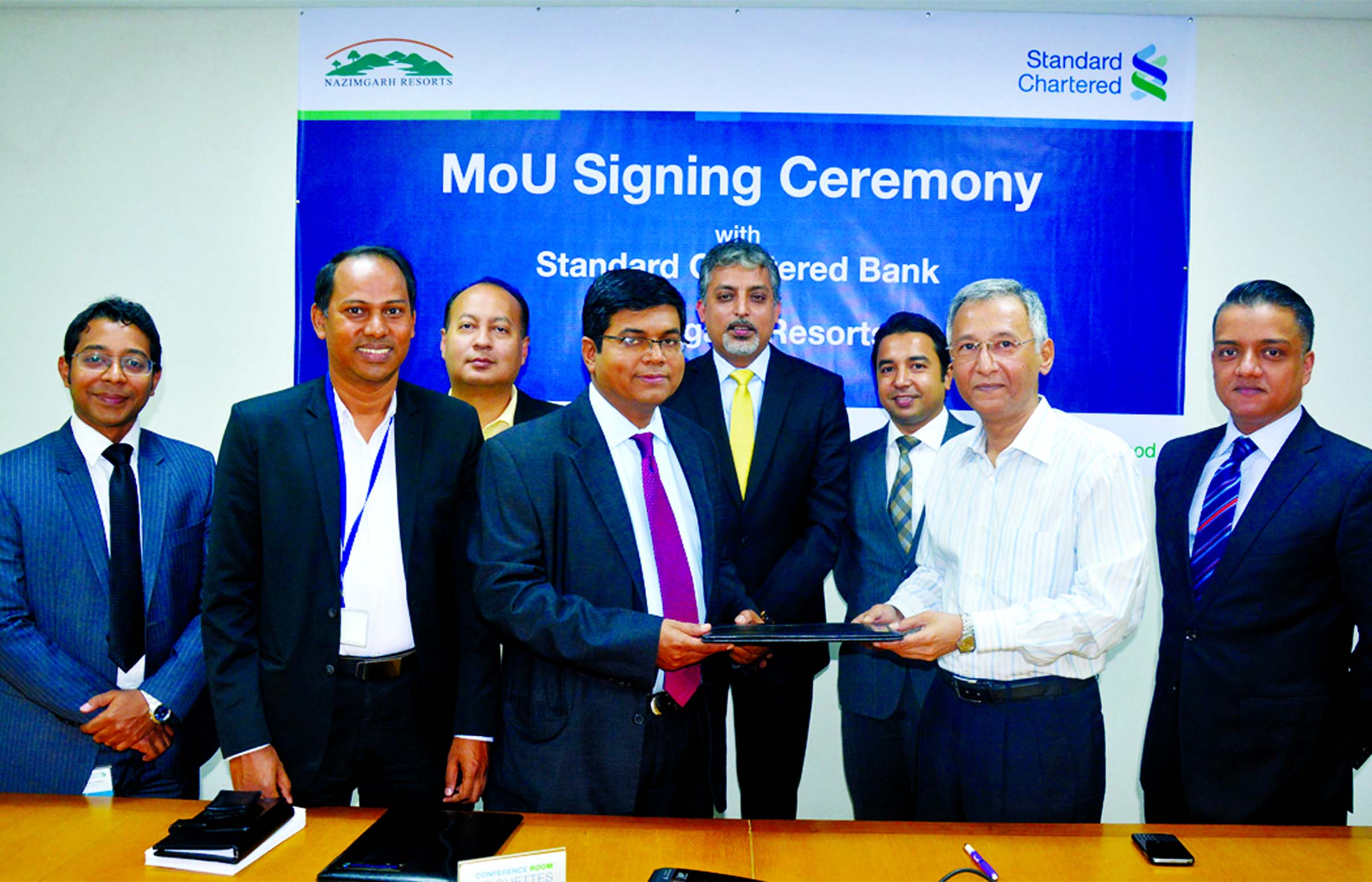 Makam E Mahmud Billah, Head of Retail Products of Standard Chartered Bank and Nazim Shafkat Choudhury, Director of Nazimgarh Resorts in Sylhet exchanging a MoU signing documents in the city recently. Under the deal, the resorts will provide a range of exclusive benefits to Credit and Debit Cardholders of the bank upto 35percent discount on published room rates. Md Mahiul Islam, Head of Brand and Marketing of the bank and other senior officials from both the organizations were present.