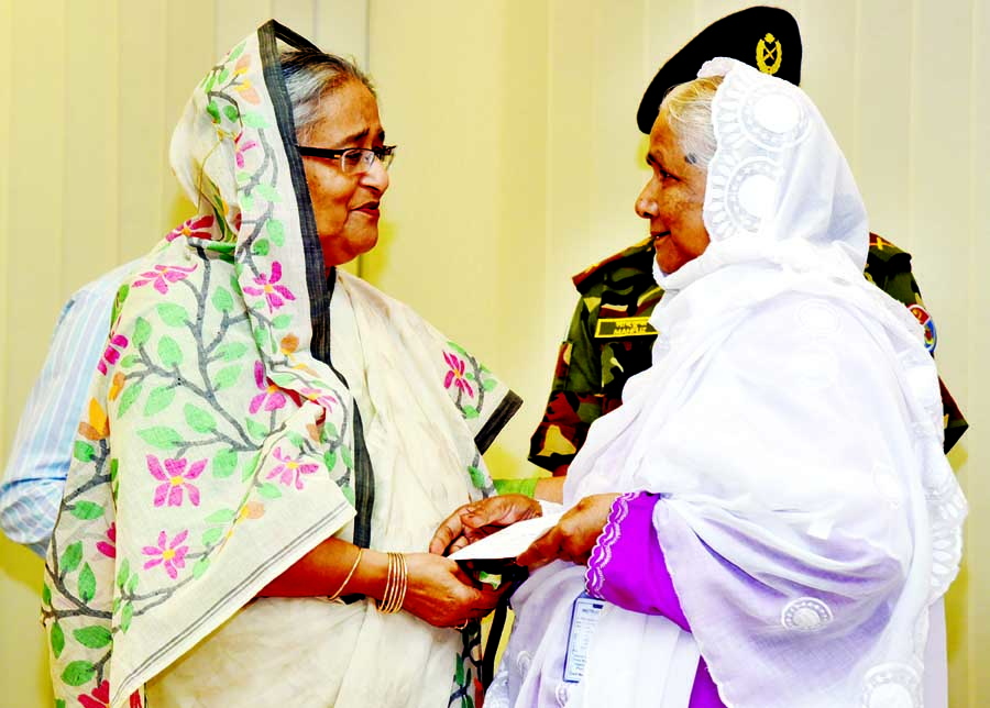 Prime Minister Sheikh Hasina handing over cheques of financial assistance among the heirs of Birshresthas and gallantry award recipient freedom fighters at her office on Sunday.