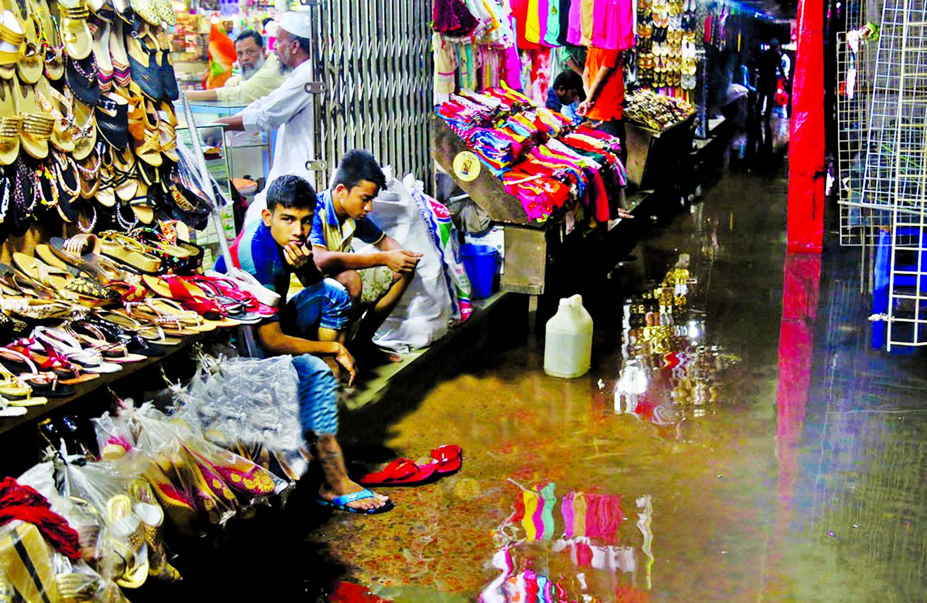 Shopowners passing idle time for the lack of buyers as the premises of shops were submerged by the rain water. The snap was taken from Mouchak Market in the city on Monday.