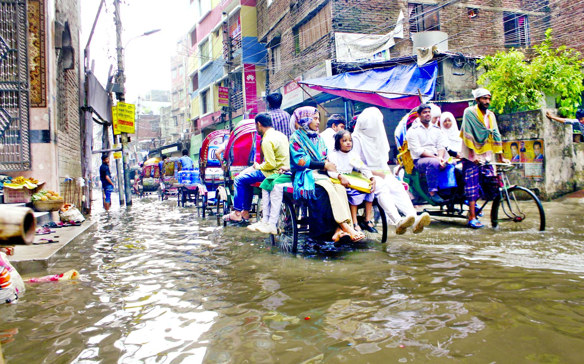 Rain water remains stagnant due to poor drainage system in different areas of the city, causing immense sufferings to commuters. Photo shows people including students passing the Nazimuddin Road with rickshaw-van pullers on Monday.