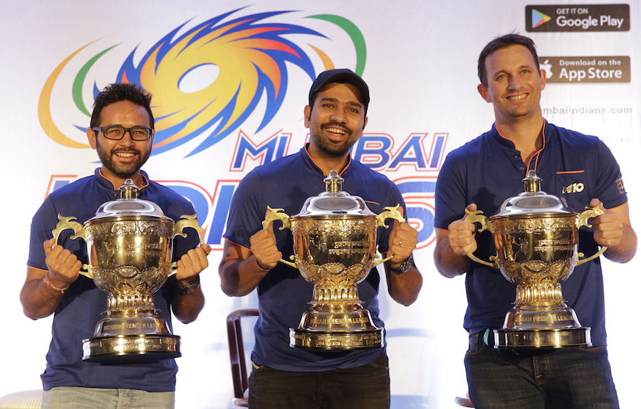 Mumbai Indians captain Rohit Sharma (center) Parthiv Patel (left) and bowling coach Shane Bond pose for a picture with the Indian Premier League (IPL) trophies from last three wins after a press conference after their IPL 2017 win in Mumbai, India on Monday.