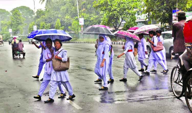 A brief drizzle brings relief to the city dwellers from the scorching heat for a while. The photo shows the students under umbrella during the rain. The snap was taken from the city's Topkhana Road on Sunday.