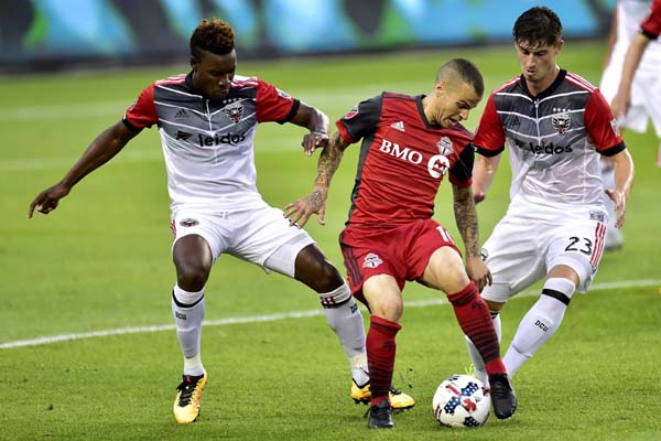 D.C. United midfielders Lloyd Sam (8) and Ian Harkes (23) work to take the ball from Toronto FC forward Sebastian Giovinco (10) during first half MLS soccer action in Toronto on Saturday.