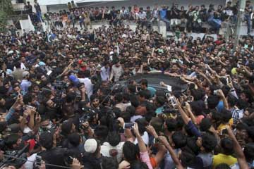 Pakistani police officers try to make way for a car carrying cricket team's skipper Sarfraz Ahmed, among a crowd gathered to welcome him outside his residence in Karachi, Pakistan on Tuesday.