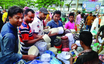 SYLHET:   Men are selecting tupi  in front of  Qudart Ullah Jamay Mosque on Thursday.