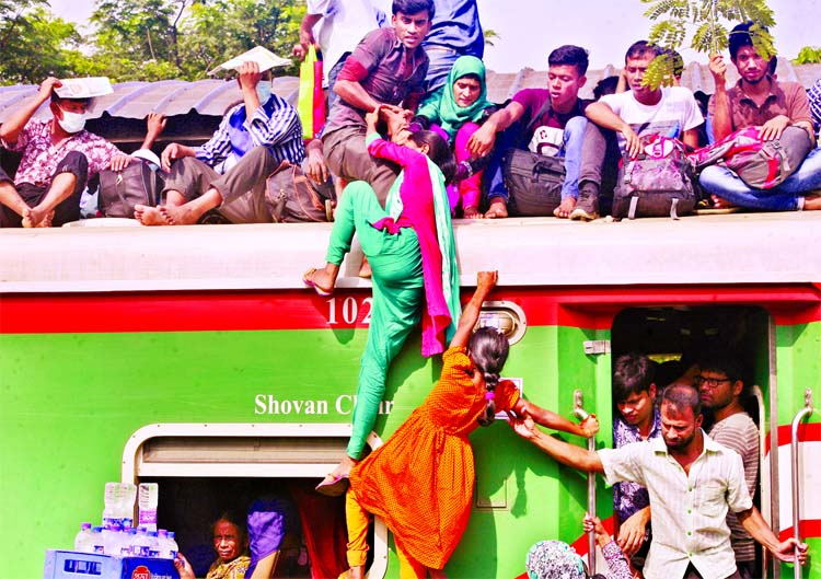 Eid home-bound women passengers are trying hard to ride the rooftop of the train taking risk of life at the Biman Bandar Railway Station on Friday.