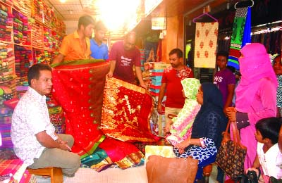 ISHWARDI (Pabna):   Both buyers and sellers are busy  at a market in Eid shopping at Ishwardi Upazila  on Friday.