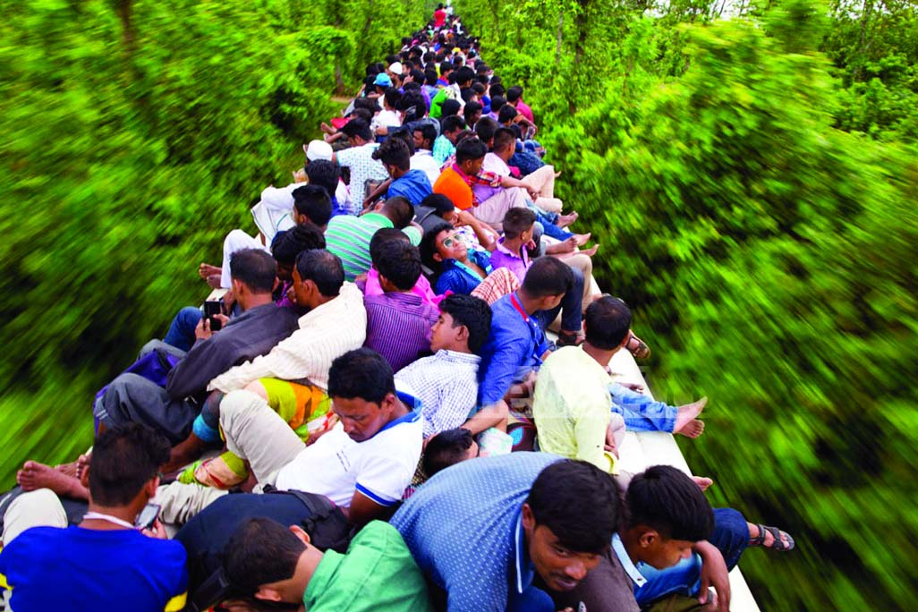 Hundreds of people of all ages ride the rooftop of a train, risking their lives left for village homes to celebrate Eid. This photo was taken from the outskirts of the city on Saturday.