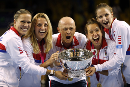 This is a Sunday, Nov. 13, 2016 file photo of the  Czech Republic team captain Petr Pala, center, and players hold the trophy after their victory against France, during the Fed Cup final in Strasbourg, eastern France.  The Davis Cup and Fed Cup are planning to combine forces into a World Cup of Tennis. A three-year deal starting in 2018 to combine the events was announced on Wednesday  by the International Tennis Federation. The changes still need to be approved at the federation's annual general meeting in August in Vietnam.