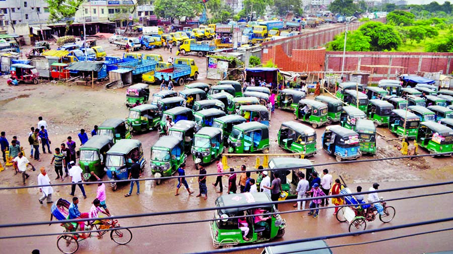 Auto-rickshaws, trucks, covered vans and lorries parked illegally around the Rayerbazar graveyard in the city narrowing the  road under the patronage of vested quarters. This photo was taken on Friday.