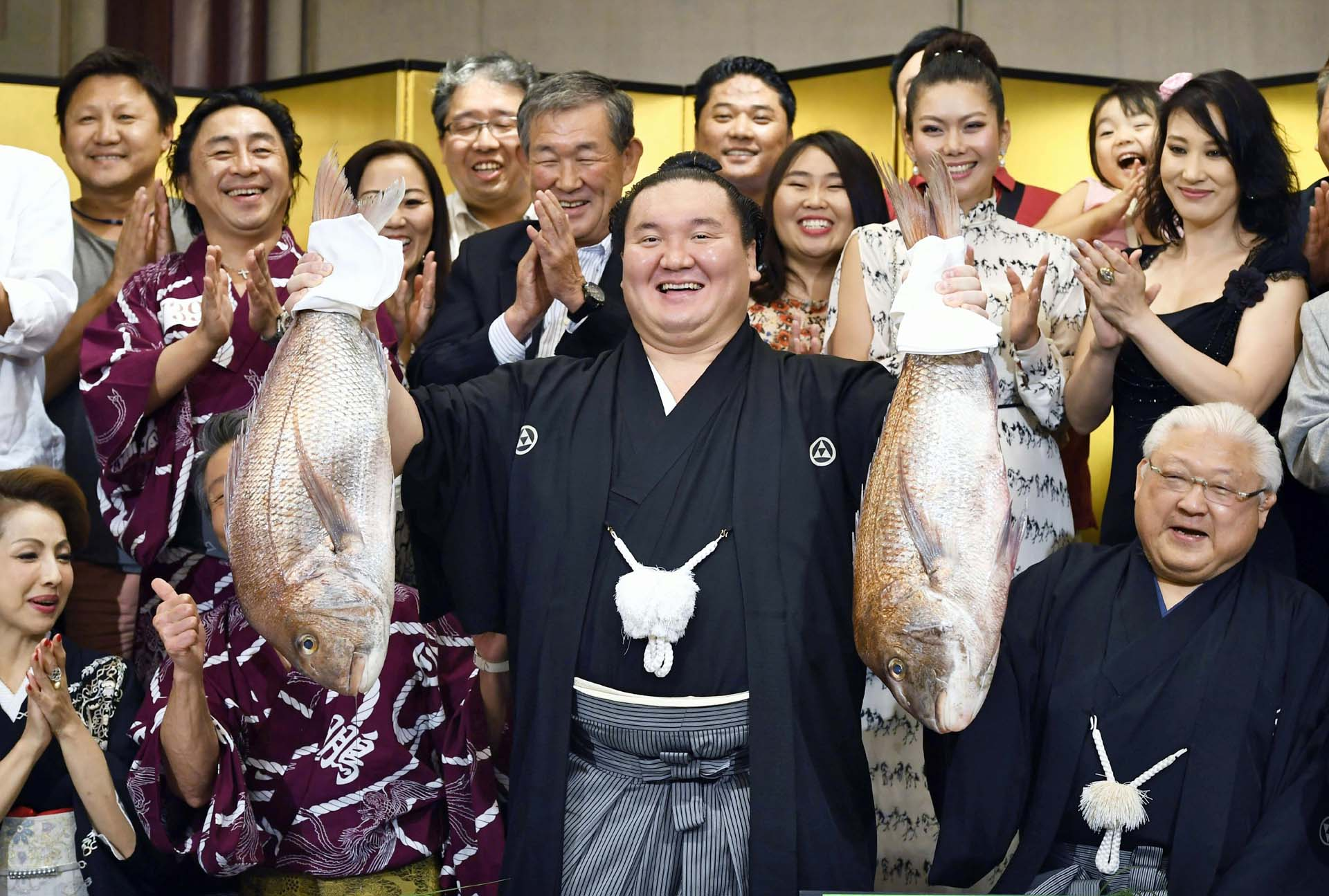 In this Sunday, July 23, 2017 photo, Mongolian grand champion Hakuho (center) celebrates after he won the Nagoya Grand Sumo Tournament in Nagoya, Aichi prefecture, central Japan. Hakuho won the 39th career title.