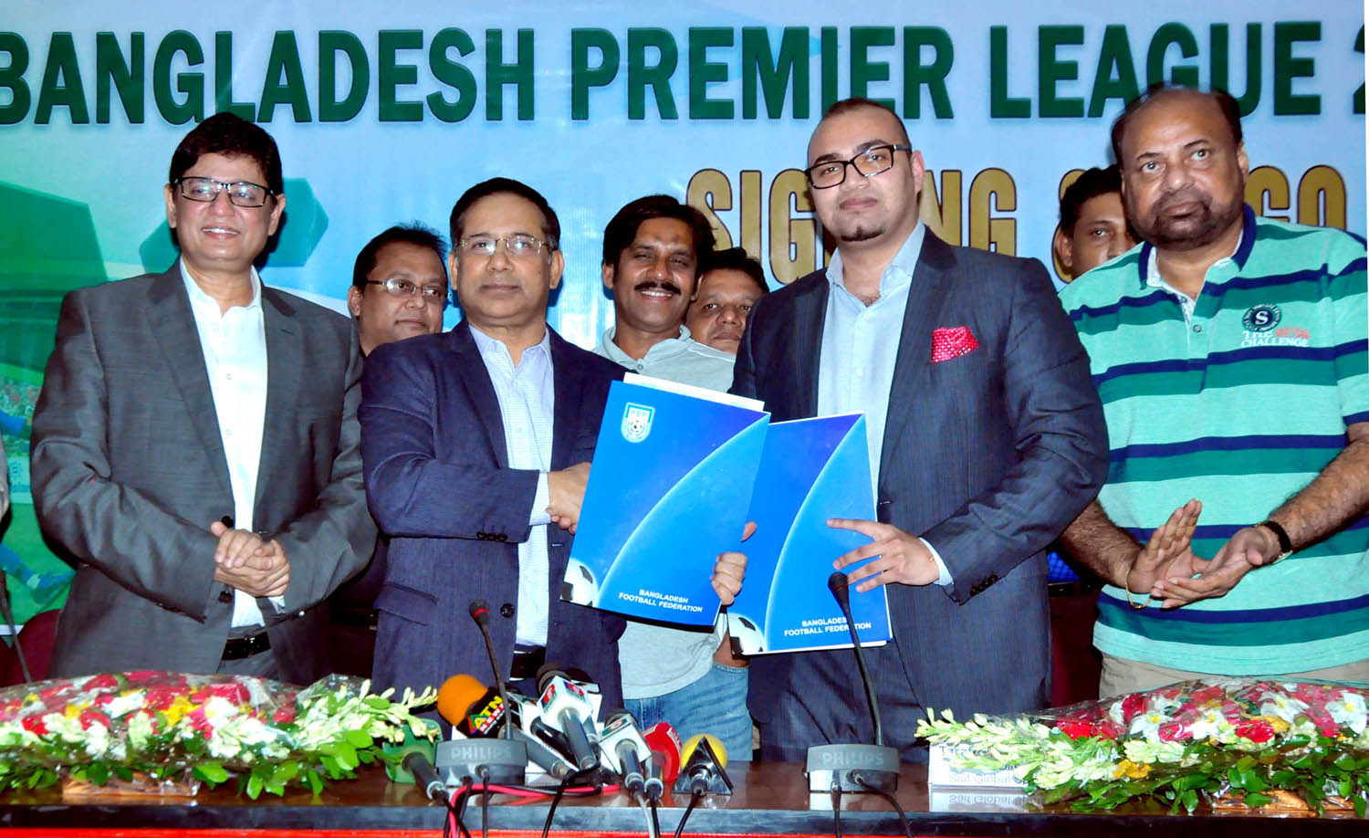 Senior Vice-President of Bangladesh Football Federation Abdus Salam Murshedy and Director of Saif Global Sports Tarafder Md Ruhul Saif exchanging papers after signing an agreement at the conference room of BFF House on Tuesday.