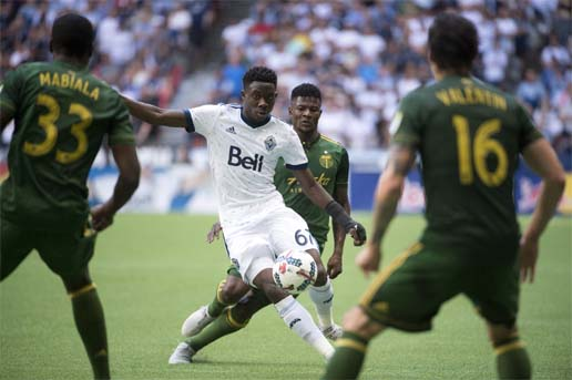 Portland Timbers forward Dairon Asprilla (second from right) gives chase as Vancouver Whitecaps forward Alphonso Davies (67) tries to get the ball around the Timbers' defense during the second half of MLS soccer game action in Vancouver, British Columbia on Sunday.