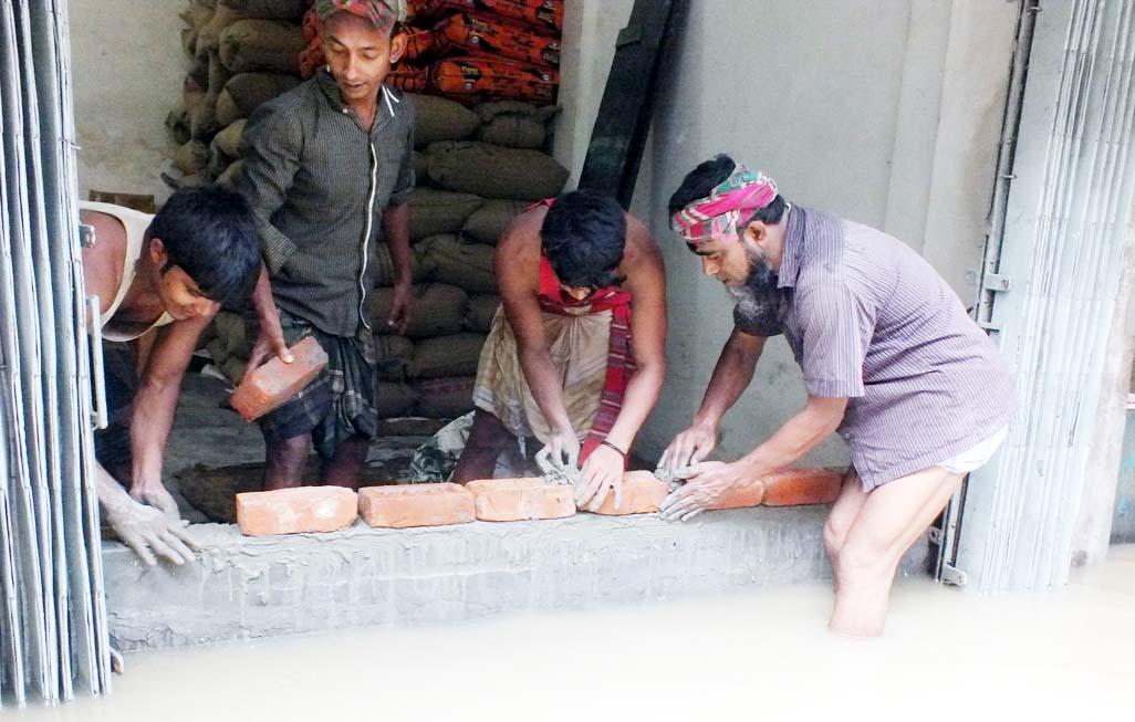 Businessman  at Khatunganj area trying to save  their shops from rain  water on Tuesday.