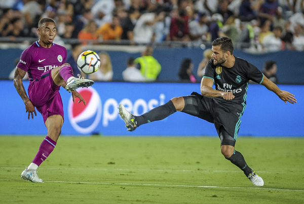 Manchester City's Gabriel Jesus (left) tries to control the ball as Real Madrid CF