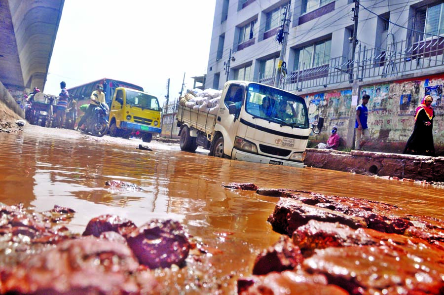 With the recession of waters from the city roads, several potholes, cracks developed, causing sufferings to commuters as vehicles facing difficulties to cross the water-logging area. This photo was taken from Jatrabari area on  Thursday.