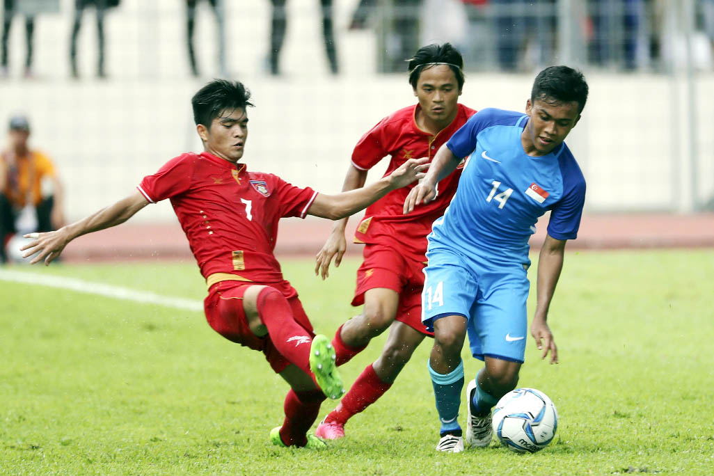 Singapore's Muhammad Hami Syahin bin Sad (right) fight for controls of the ball with Myanmar's Hlaing Bo Bo during opening match of Men's Soccer of South East Asian Games in Selayang, Malaysia on Monday.