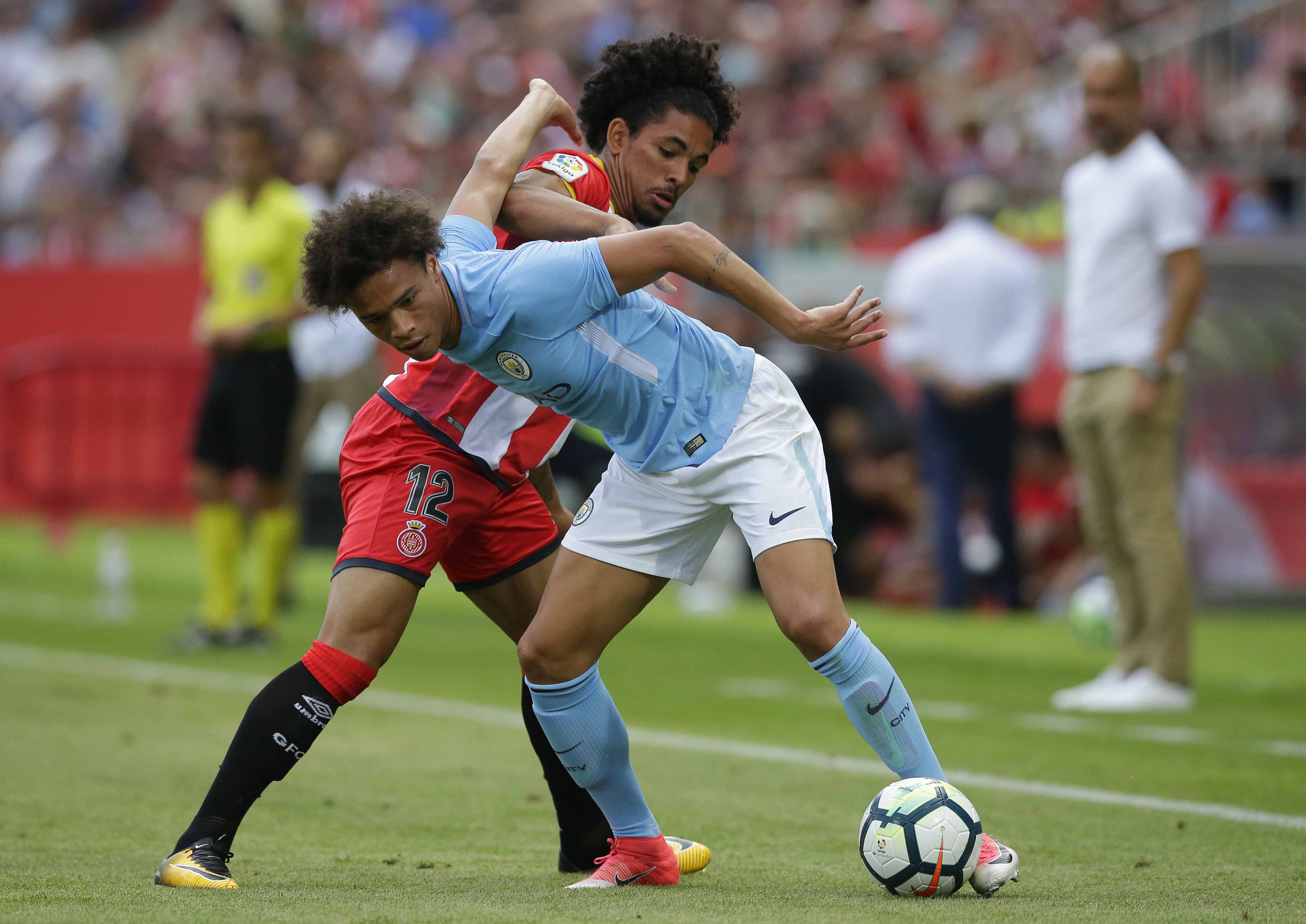 Manchester City's Leroy Sane (right) duels for the ball against Girona's Douglas Luiz during the Costa Brava trophy friendly soccer match between Girona and Manchester City at the Montilivi stadium in Girona, Spain on Tuesday