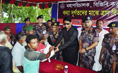 DINAJPUR: Whip of the Jatiya Sangsad Iqbalur Rahim MP and DG of BGB Maj Gen Abul Hossain  distributing relief goods  at Kamdevpur in Biral Upazila on Thursday.