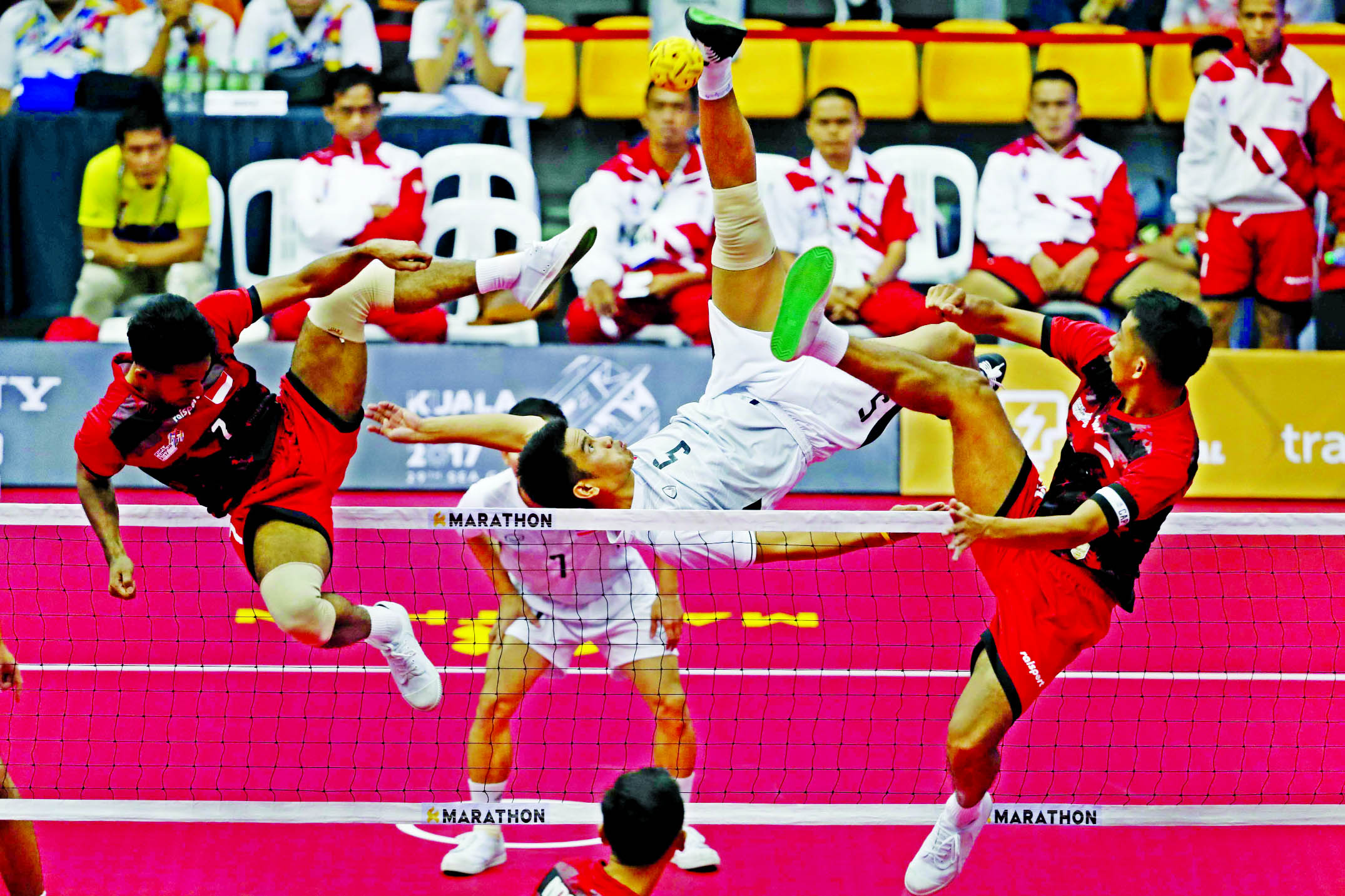 Thailand's Pornchai Kaokaew (center) kicks a ball against Indonesia's Saiful Rijai (left) and Syamsul Hadi during the men's Sepak Takraw Regu competition at South East Asian Games in Kuala Lumpur, Malaysia on Friday.