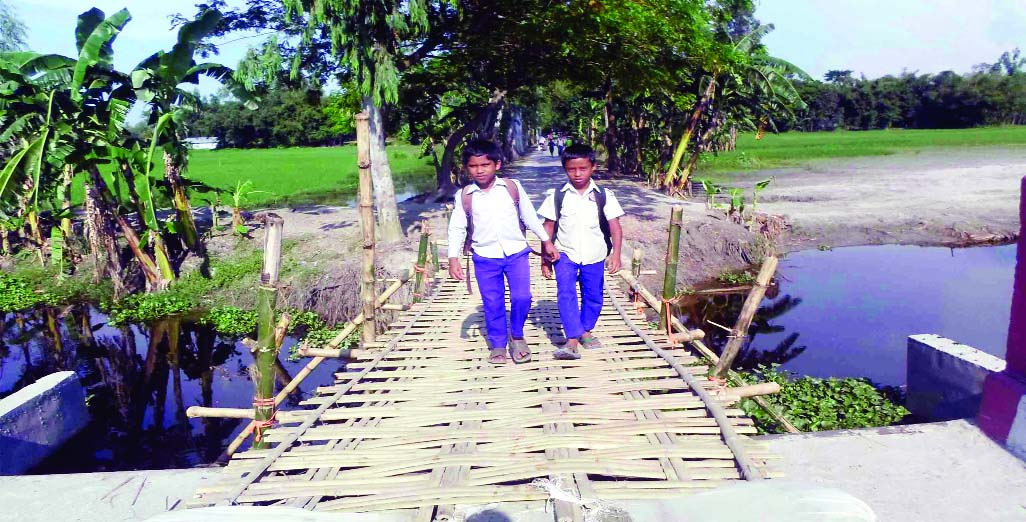 SUNDARGANJ (Gaibandha): People are using  bamboo made bridge at the damaged portion of Ram Dakuya - Panchanoth Bridge in Sundarganj Upazila which needs immediate repair. This snap was taken on Tuesday.