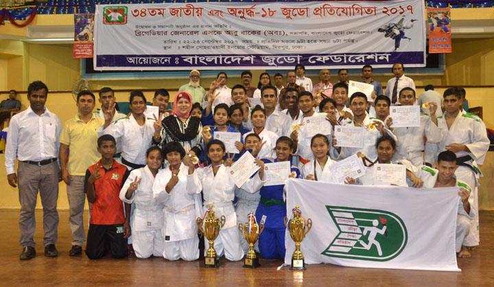 Members of BKSP team, who became champion in Under-16 two-day long Judo Competition pose for photo with the trophy and guests at the Shaheed Suhrawardy Indoor stadium in Mirpur on Saturday.