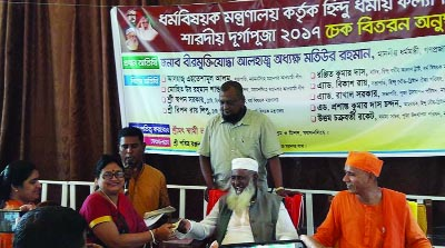 MYMENSINGH: Religious Affairs Minister Prof Md Matiur Rahman handing over donation for Durga Puja to the authority of Ramkrishna Mission in Mymensingh on Saturday. Among others, Mission Chief Swami Bhakti Pradanandera was present as special guest.