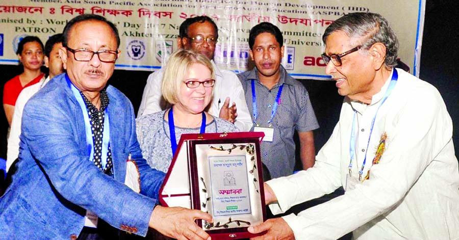 Primary and Mass Education Minister Mostafizur Rahman handing over citation to Bishwa Sahitya Kendra President Prof Abdullah Abu Sayeed for his role in education at TSC auditorium of Dhaka University on Tuesday in observance of World Teachers' Day.