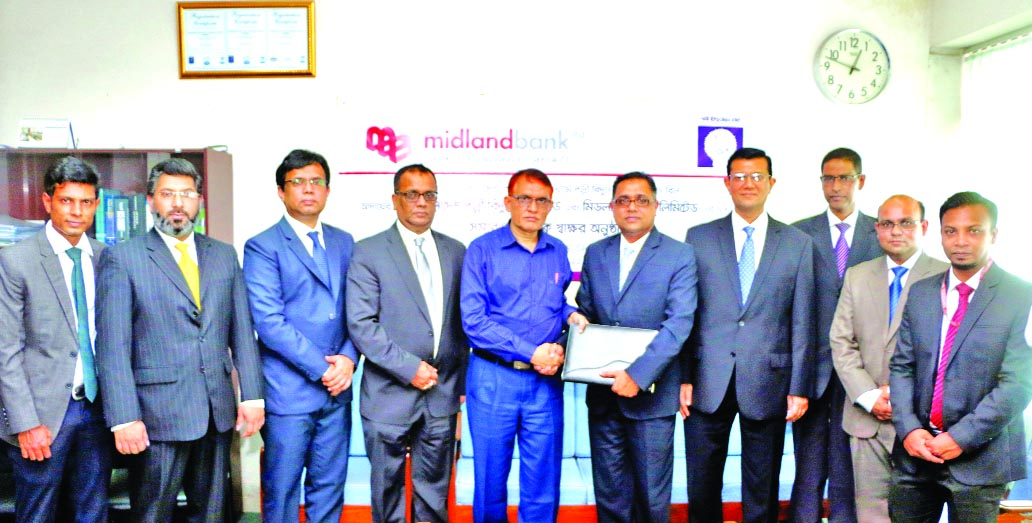 Md. Ridwanul Hoque, Head of Retail Distribution of Midland Bank Limited and Hossain Patoari, Director (Finance) of Bangladesh Rural Electrification Board (BREB) exchanging an agreement signing documents at BREB head office in the city on Monday. Under the deal, the bank will now collect bills from REB customers through the bank's Agent Banking. Md. Ahsan-uz Zaman, Managing Director of the bank and high officials of BREB were present.