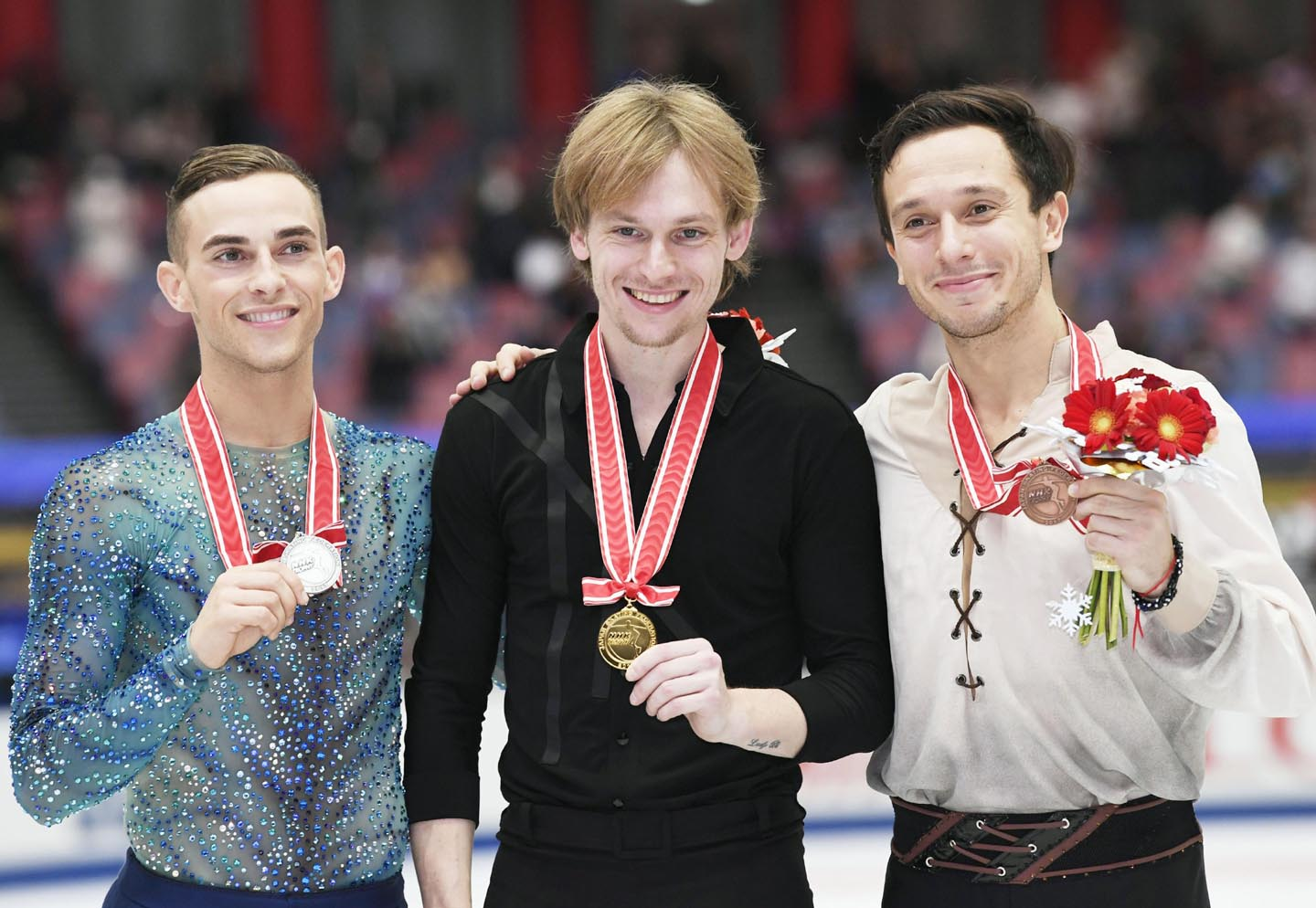 Sergei Voronov of Russia (center)  poses with the gold medal, with second placed Adam Rippon of the United States (left) and third-placed  Alexei Bychenko of Israel (right) at the NHK Trophy figure skating on Saturday in Osaka, western Japan.
