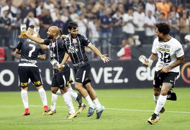 Corinthians players carry drinks as they celebrate winning the Brasileirao soccer championship title, after their match with Fluminense in Sao Paulo, Brazil on Wednesday. Corinthians won 3-1.