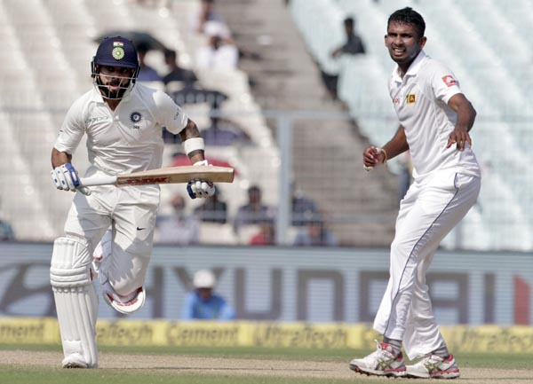 Sri Lanka's Dasun Shanaka (right) watches India's captain Virat Kohli run between the wickets during the fifth day of their first test cricket match in Kolkata, India on Monday.