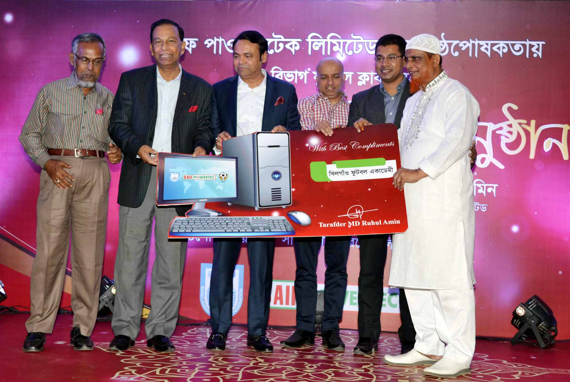 Secretary of Youth and Sports of Bangladesh Awami League Harunur Rashid (second from the left) and Chairman of the Saif Powertec Limited Tarafder Md Ruhul Amin (third from the left) distribute the computer to a representative of the Dhaka Metropolis Third Division Football League at Dhaka Metropolis Football League Committee conference room in the Bangabandhu National Stadium on Monday.
