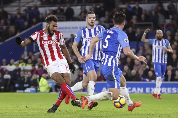 Stoke City's Eric Maxim Choupo-Moting (left) scores his side's first goal of the game against Brighton & Hove Albion during their English Premier League soccer match at the AMEX Stadium in Brighton, England on Monday.