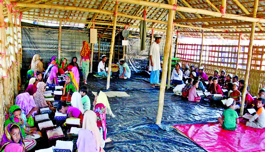 The displaced Rohingya children are learning the Quran at a mosque in the Balukhali temporary camp under Ukhiya upazila in Cox's Bazar district.