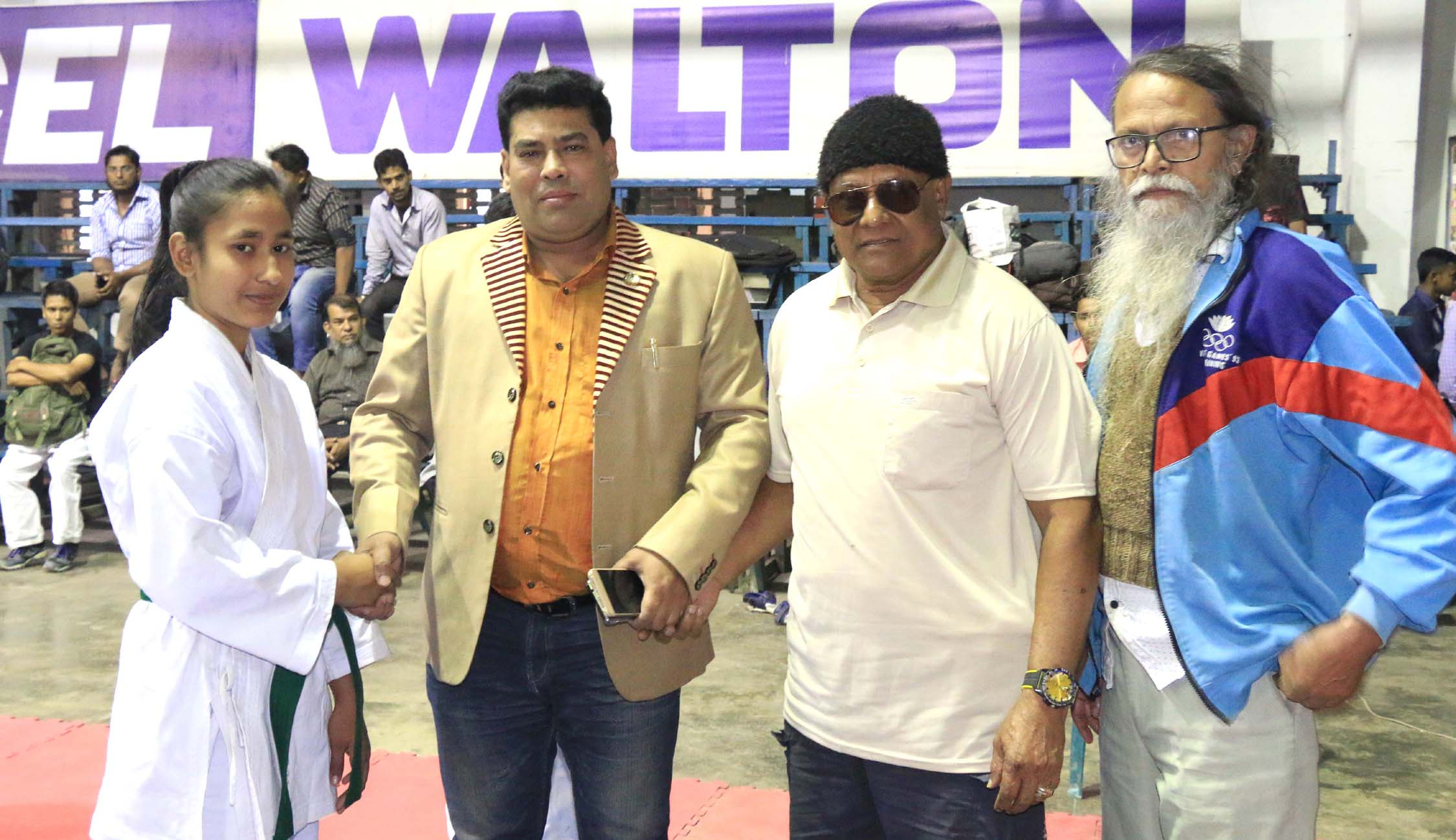 Operative Director (Head of Sports & Welfare Department) of Walton Group FM Iqbal Bin Anwar Dawn (second from left) shaking hands with a participant of Walton National Martial Art Competition at the gymnasium of National Sports Council on Wednesday.