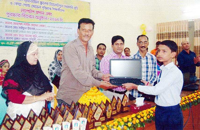 Founder Chairman of BRC Ideal Kindergarten School of Raozan, Chittagong Nurul Alam Chowdhury  handing over  laptop to a successful talent-pool scholarship awarded student of the school  at the annual prize giving ceremony of the school recently.