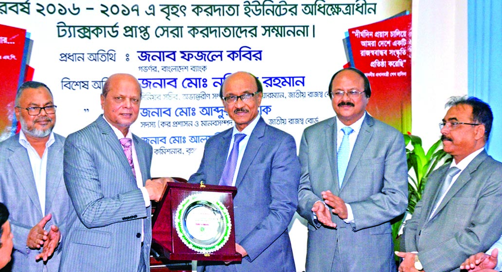 Md. Abdul Hamid Miah, Managing Director of Islami Bank Bangladesh Limited, receiving a crest from Bangladesh Bank Governor Fazle Kabir, for being highest taxpayer in the banking sector in 2016-2017 at a programme organized by Large Taxpayer Unit in the city on Tuesday. NBR Chairman Nazibur Rahman, among others were also present.