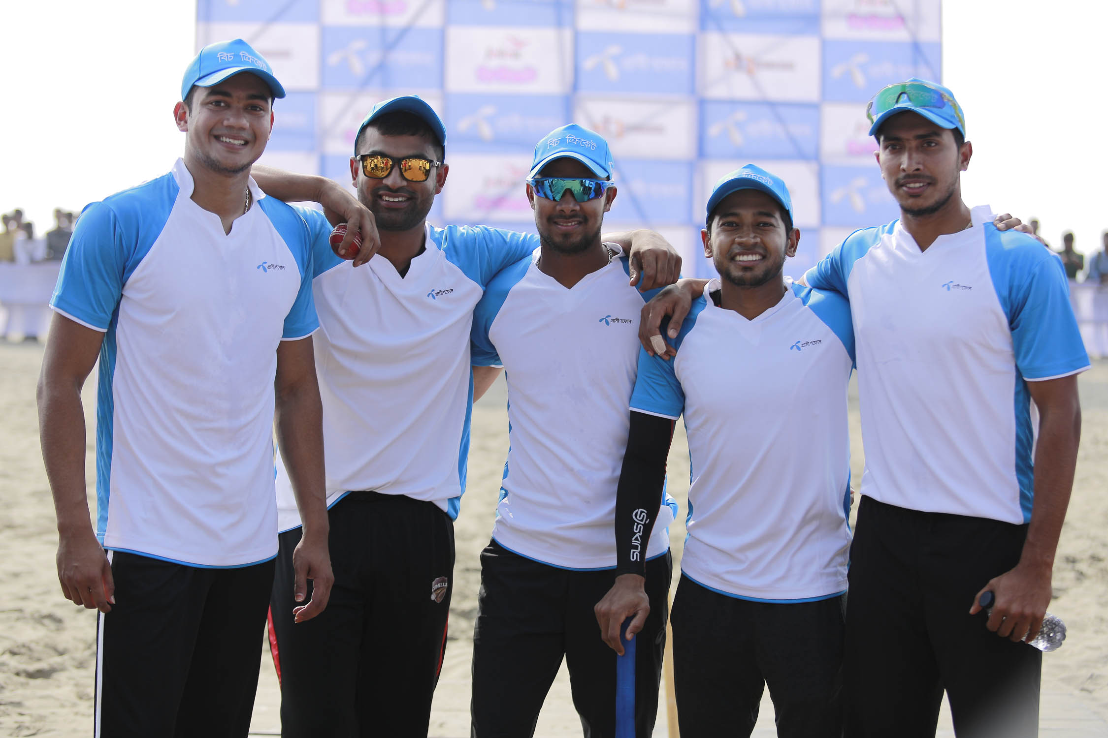 The national cricketers pose for a photo session before taking part in the exhibition cricket match with their fans at the Cox's Bazar Sea Beach on Wednesday.