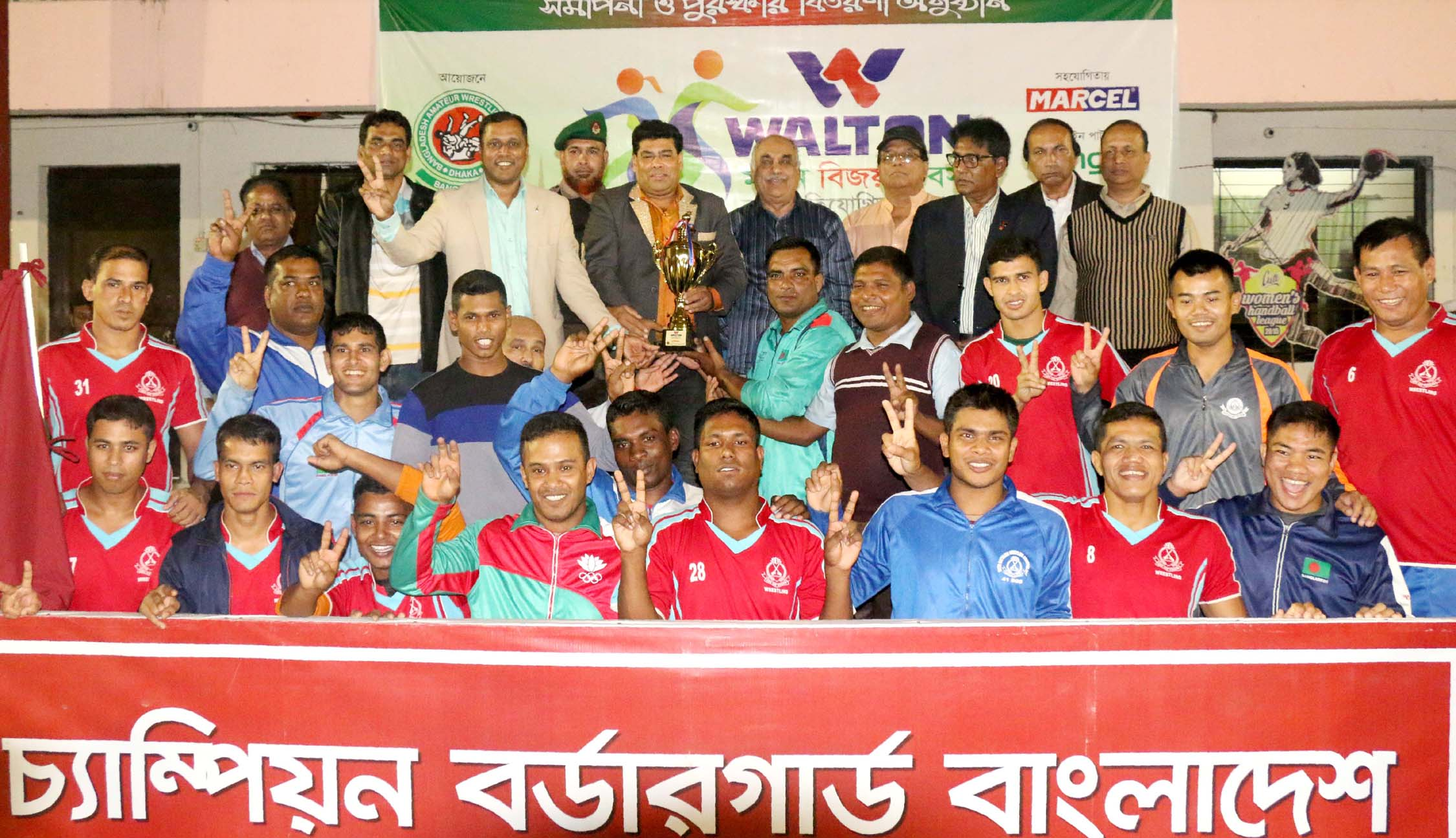 Members of Border Guard Bangladesh, the champions of the Men's Group of the Walton Victory Day Wrestling Competition with the guests and officials of Bangladesh Amateur Wrestling Federation pose for a photo session at the Shaheed (Captain) M Mansur Ali National Handball Stadium on Monday.