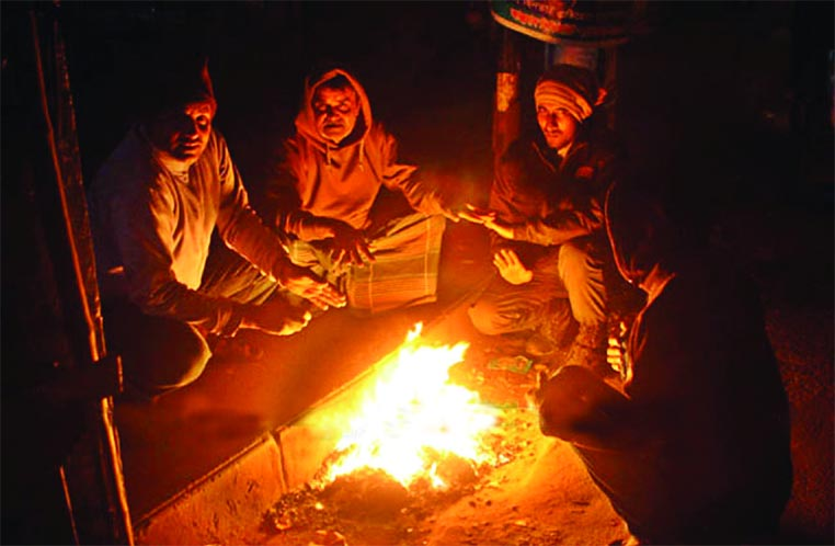 Cold-stricken poor people warm themselves sitting around a fire ...